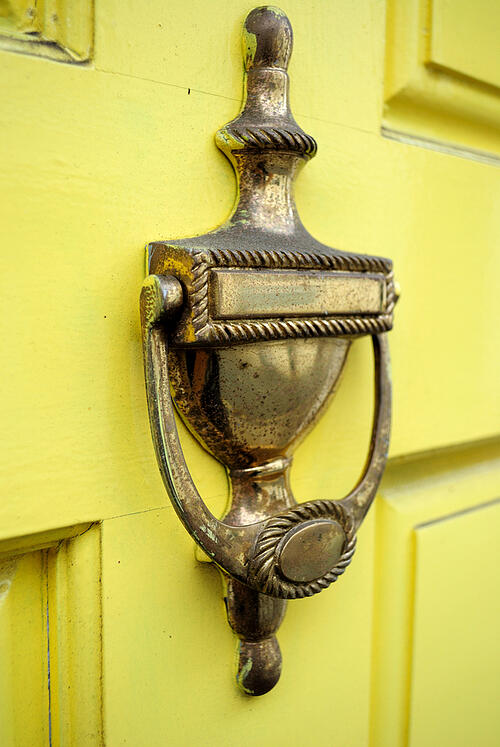 Door knock on a yellow wooden door